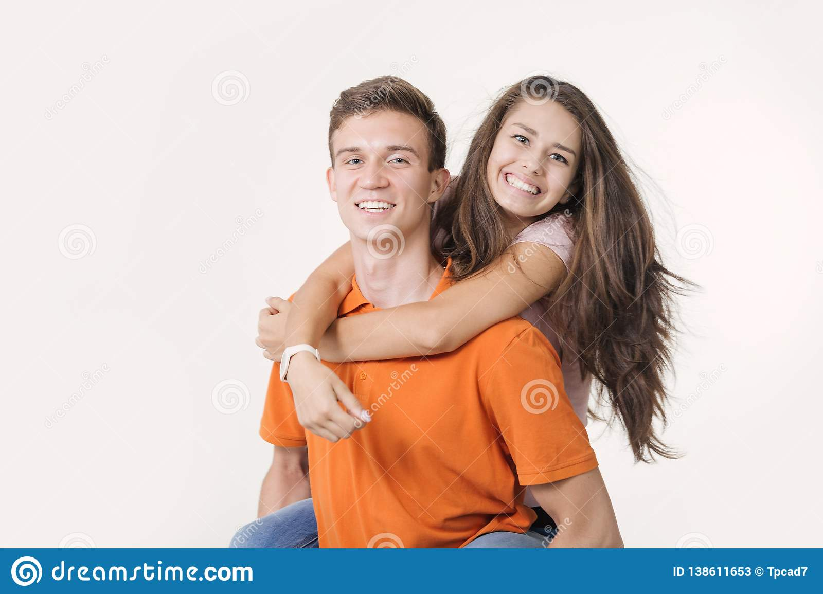 Happy lovely couple hugging and smiling looking at camera on white background