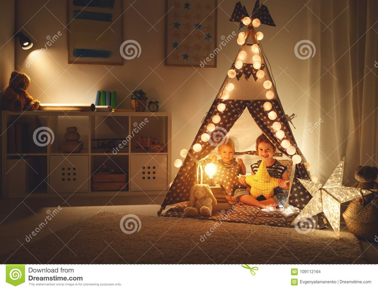Happy loving children brother and sister play in dark tent in playroom at home