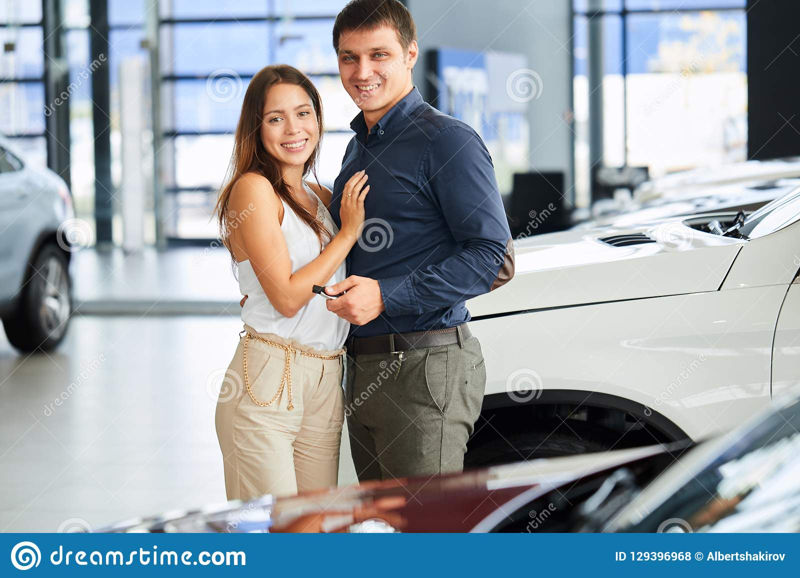 Happy Loving Couple Embracing Near Their New Luxury Car At