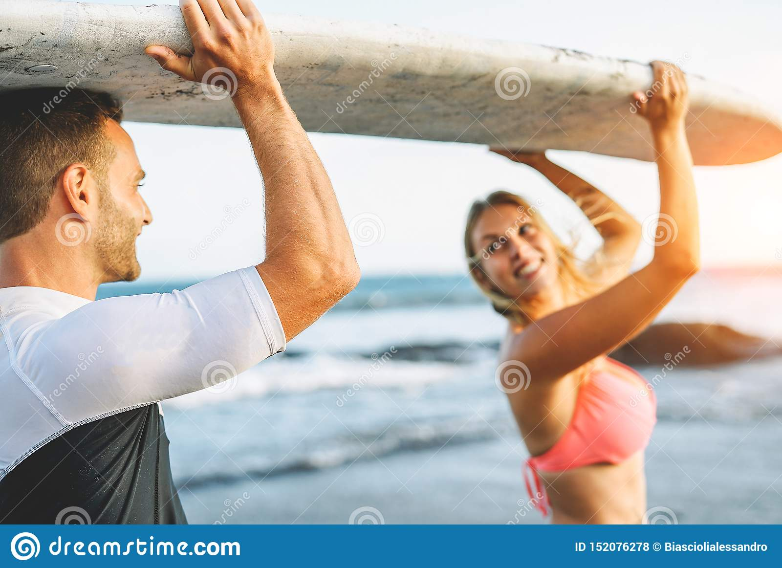 Happy loving couple holding a surfboard and looking each other - Friends having fun surfing during a vacation
