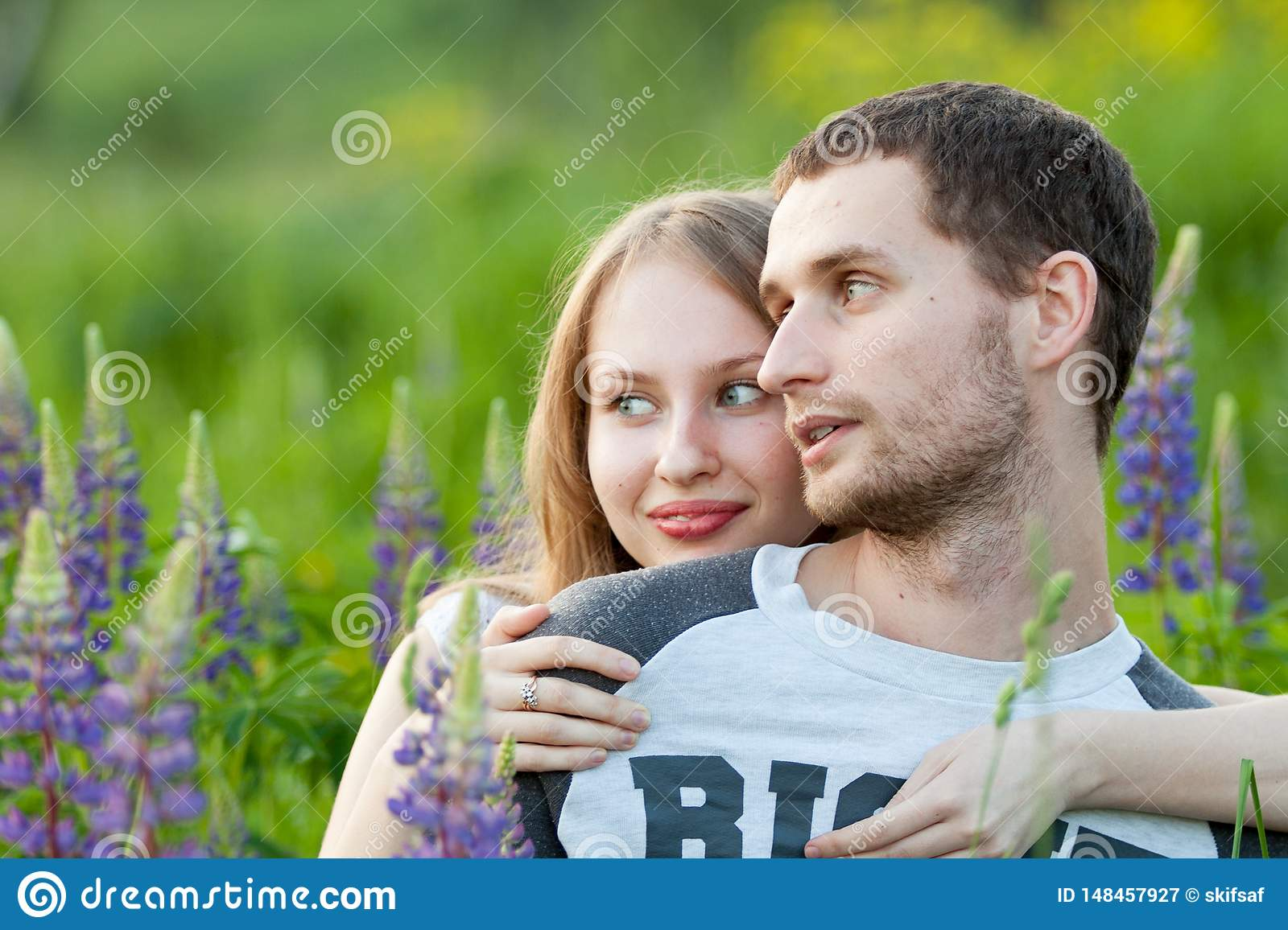 Happy loving couple hugging in field of lupine