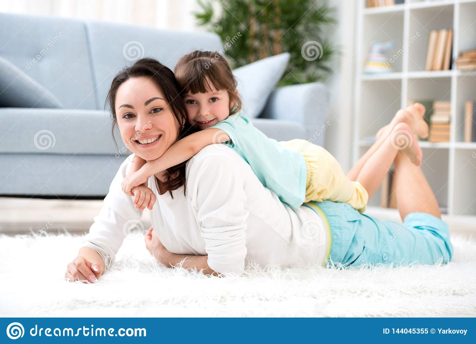 Happy loving family. Beautiful mother and little daughter have fun, play in the room on the floor, hug, smile and fool around