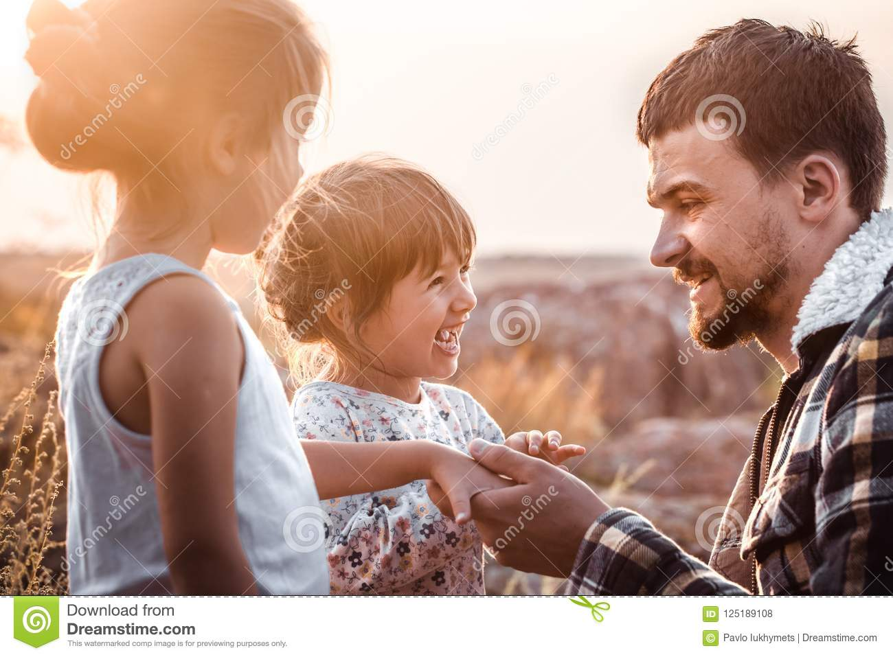 Dad playing with two little cute daughters