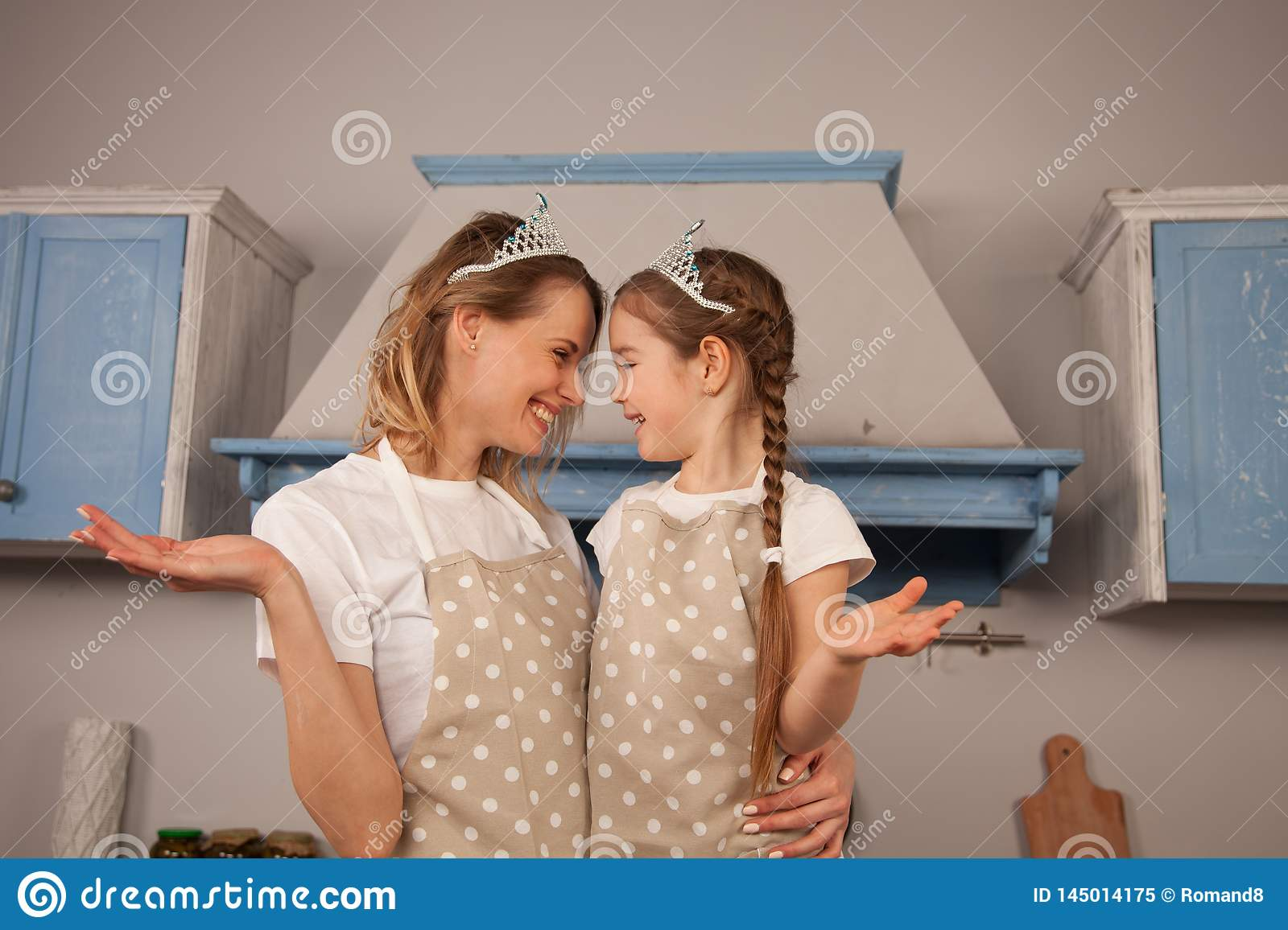 Happy loving family in the kitchen. Mother and child daughter girl are having fun wearing crowns, looking at each other