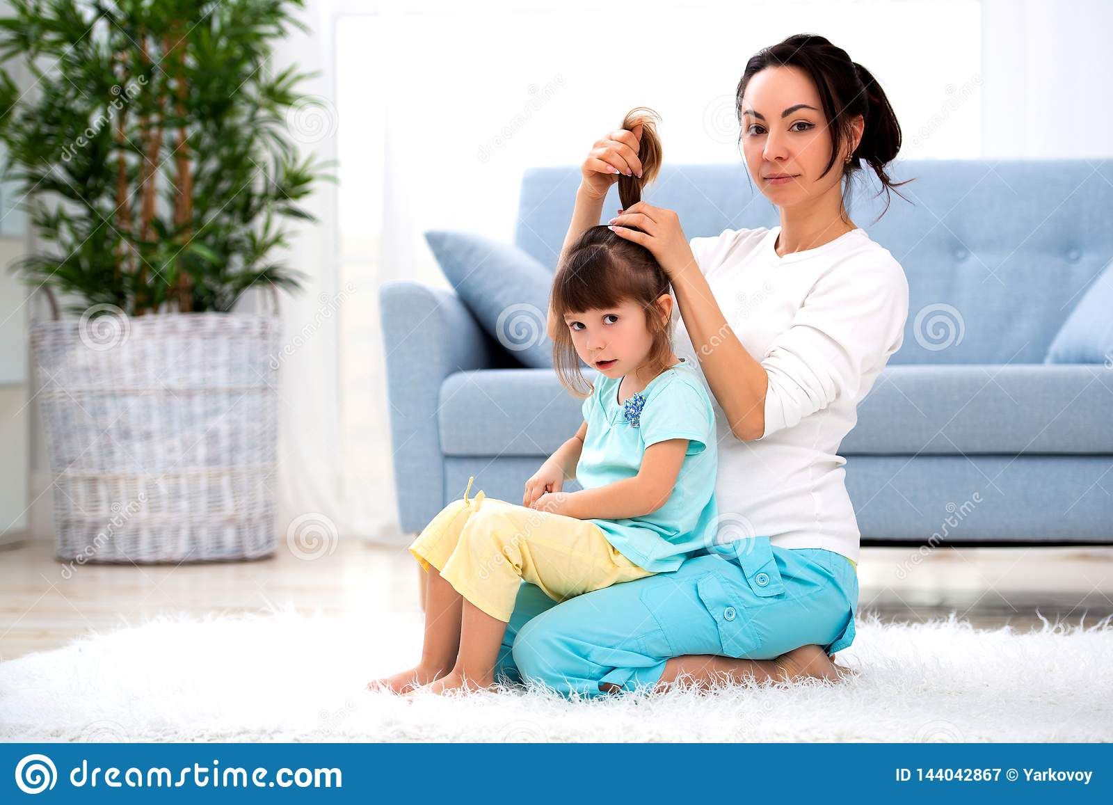 Happy loving family. Mother is combing her daughter`s hair sitting on the carpet on the floor in the room