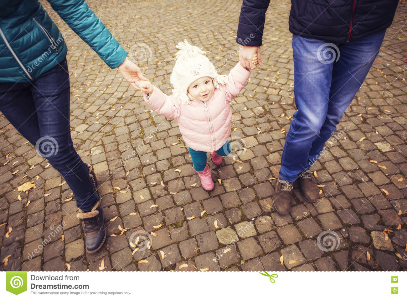 Happy loving family(mother, father and little daughter kid) outdoors walking having fun on a park in autumn season. Fallen yellow