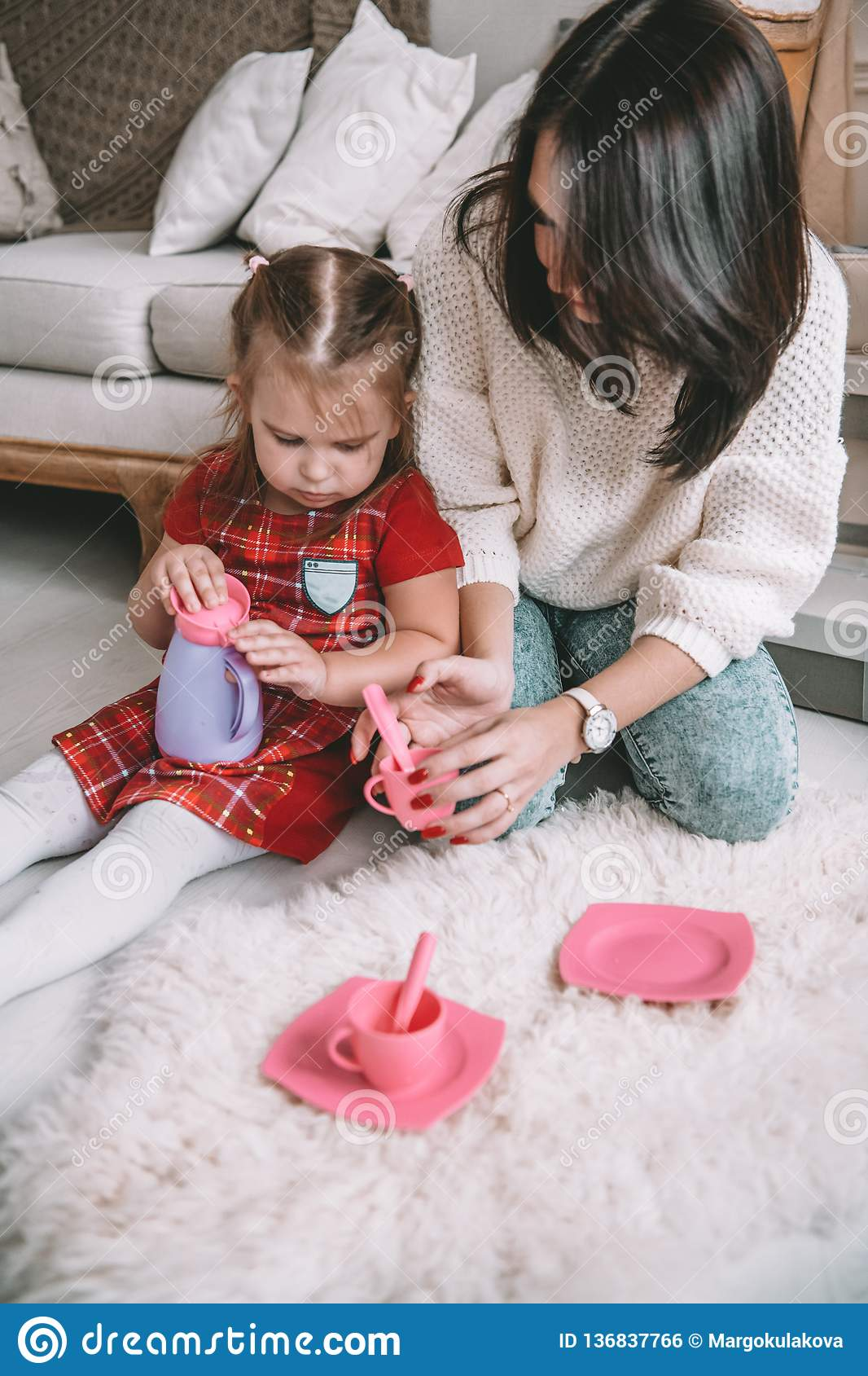 Happy loving family. Mother and her daughter girl play tea-party and drink tea from cups in children room. Funny mom and