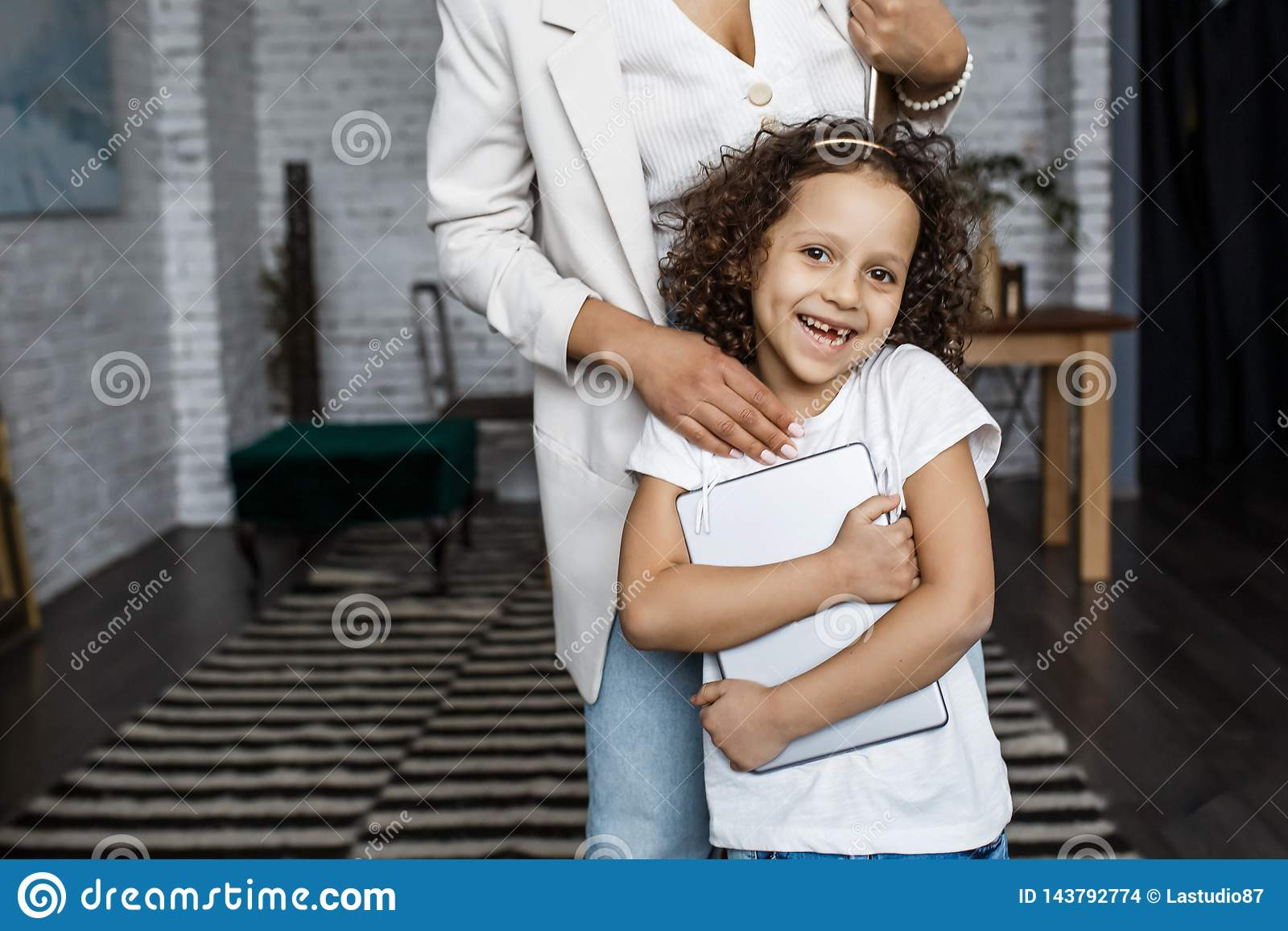 Happy loving family. Young mother and her daughter girl play in kids room. Funny mom and lovely child are having fun with tablet