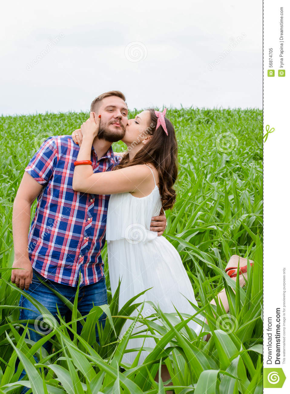 Happy loving young adult couple spending time on the field on sunny day
