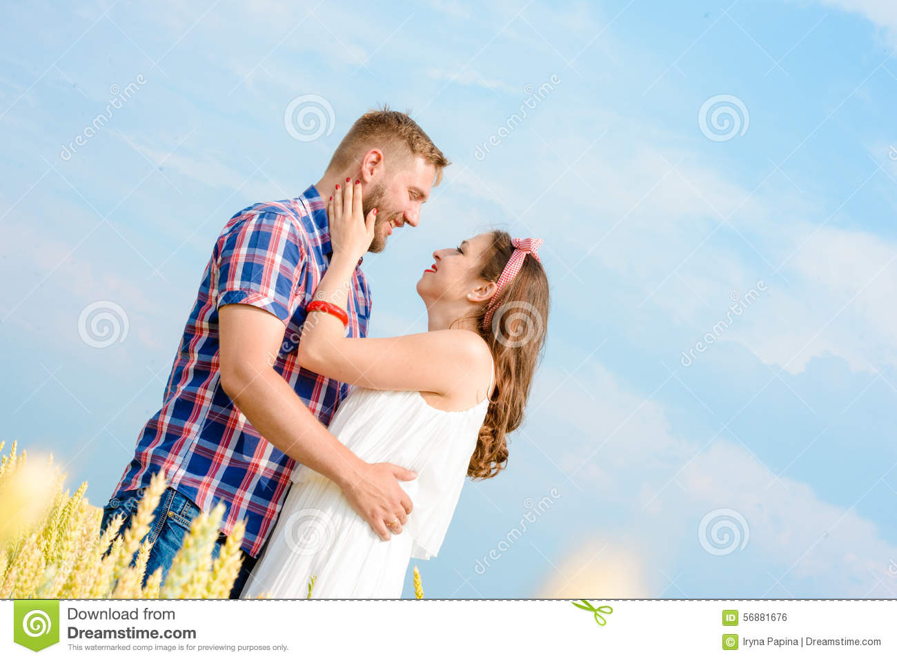 Happy loving young adult couple spending time on the field on sunny day.