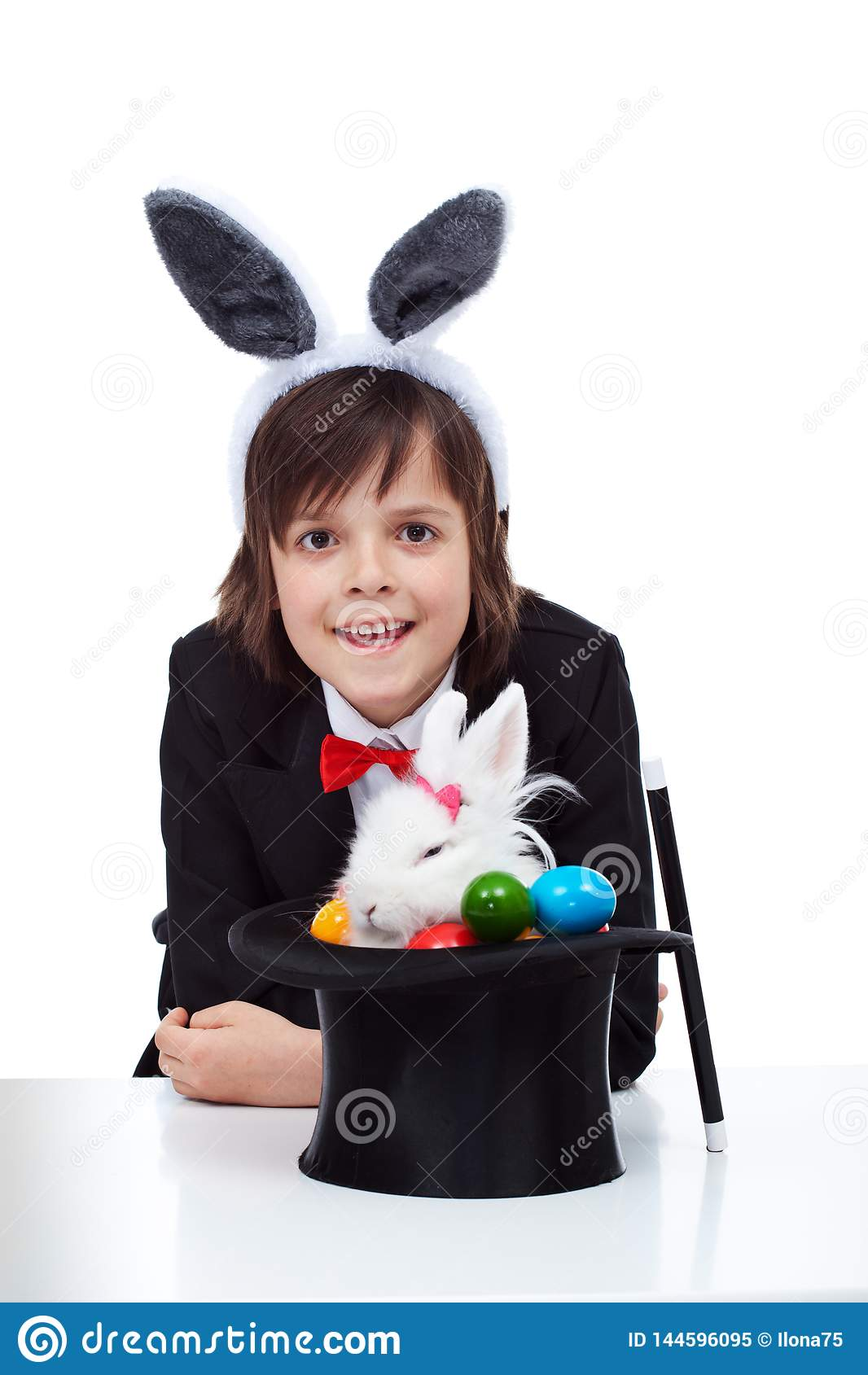 Happy magician boy smile after successfully pulling a grumpy easter bunny from the hat