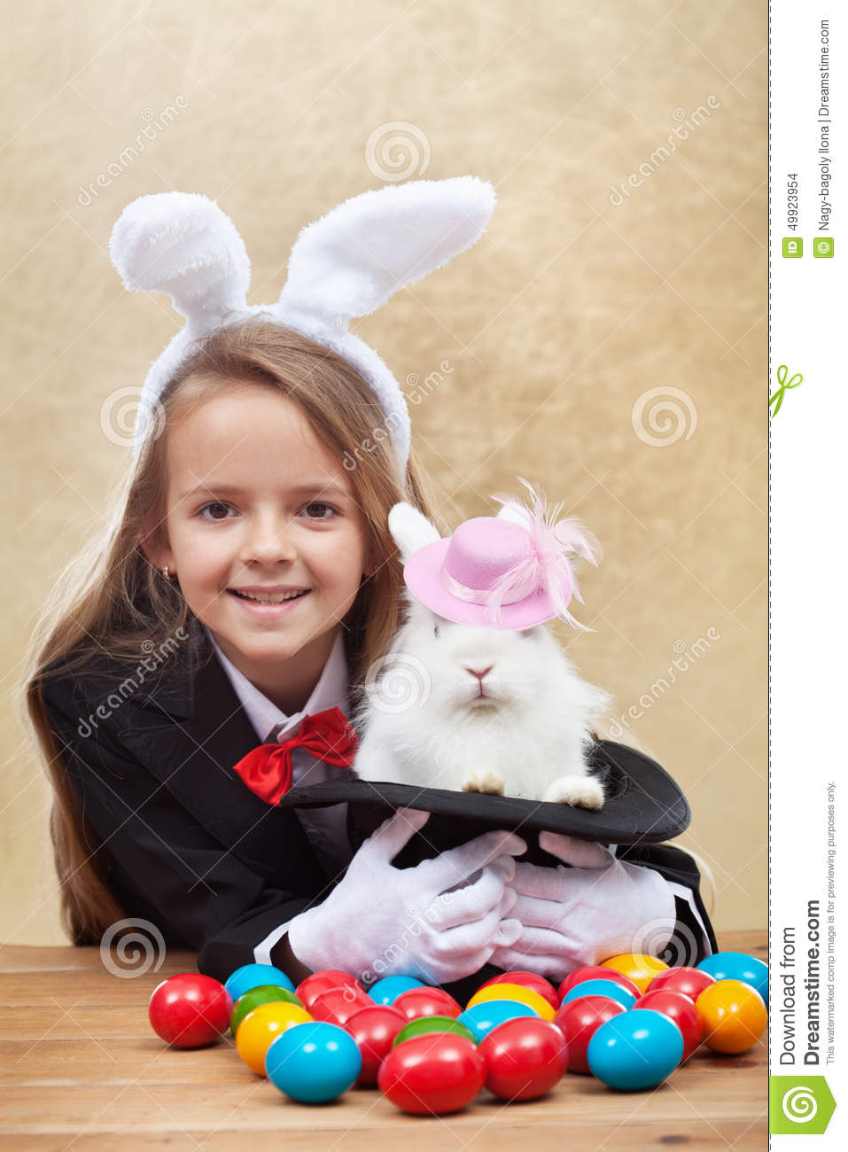 Happy magician girl holding cute bunny in magic hat