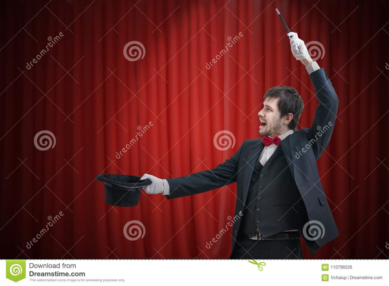 Happy magician or illusionist is showing magic trick. Red curtains in background