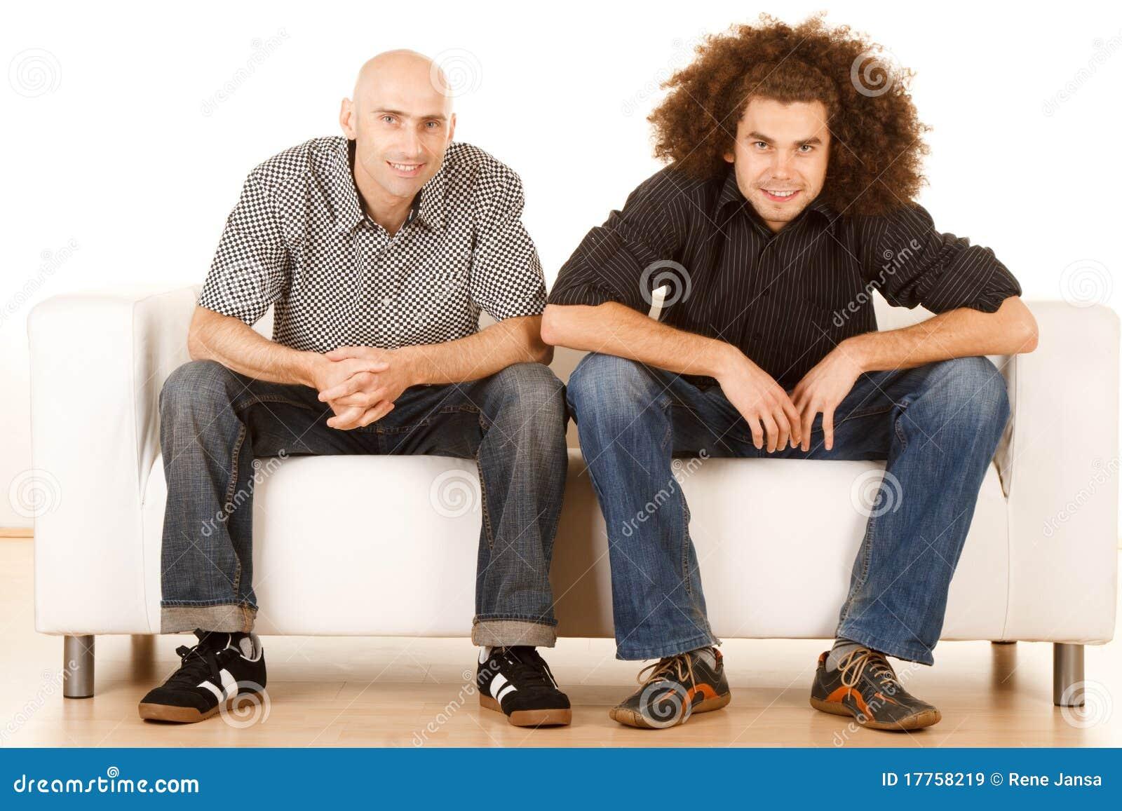 Happy male friends on sofa