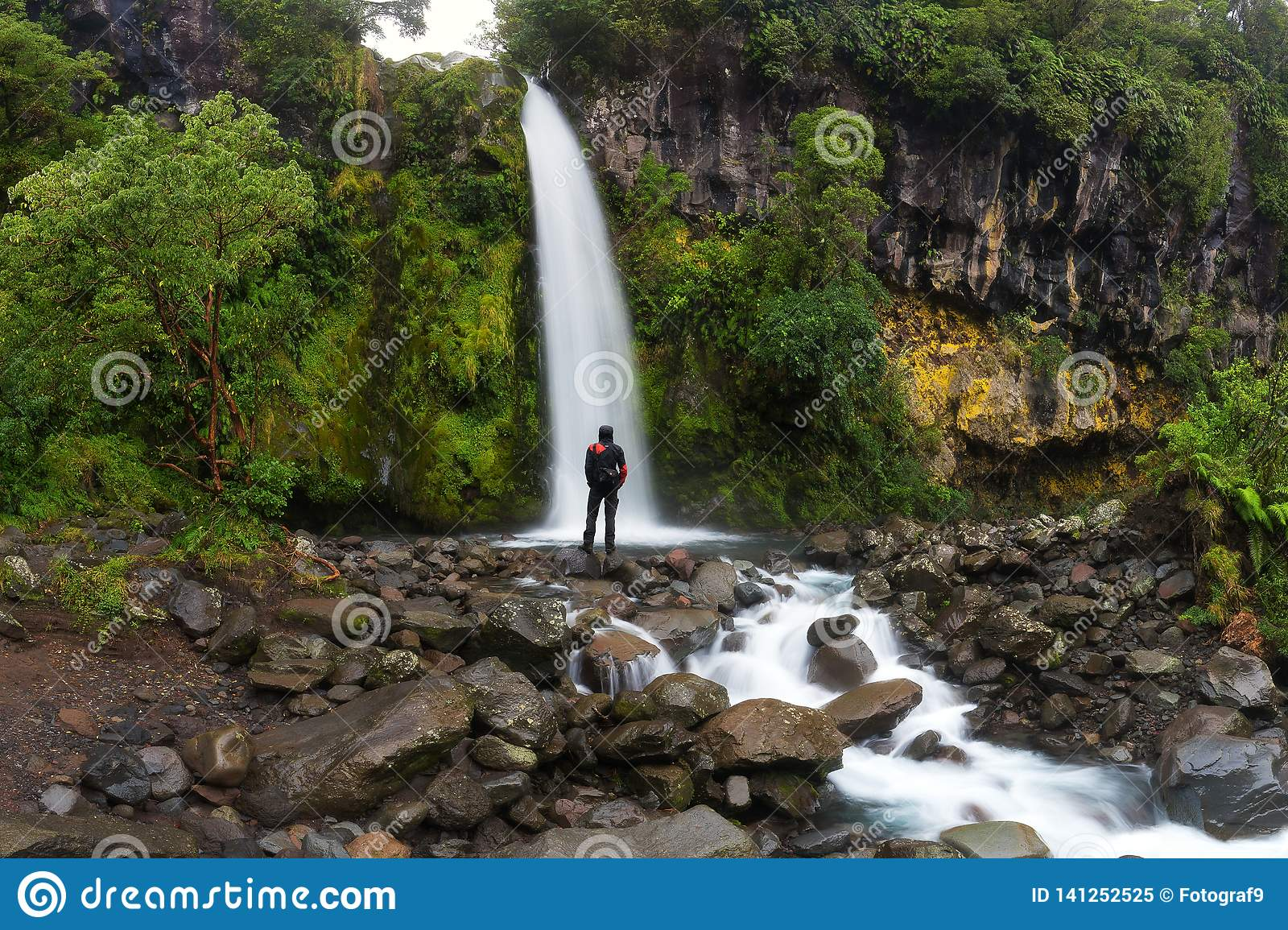 Happy man backpacker enjoying amazing tropical waterfall in New Zealand. Travel Lifestyle and success concept