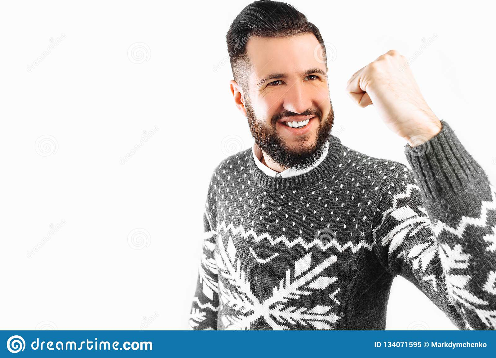 Happy man with a beard, a man depicts a gesture of victory and success