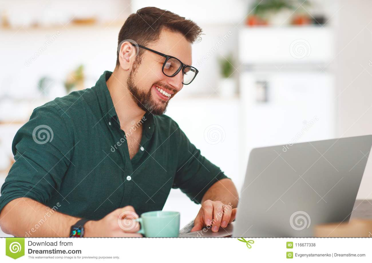 Happy man businessman, freelancer, student working at computer a