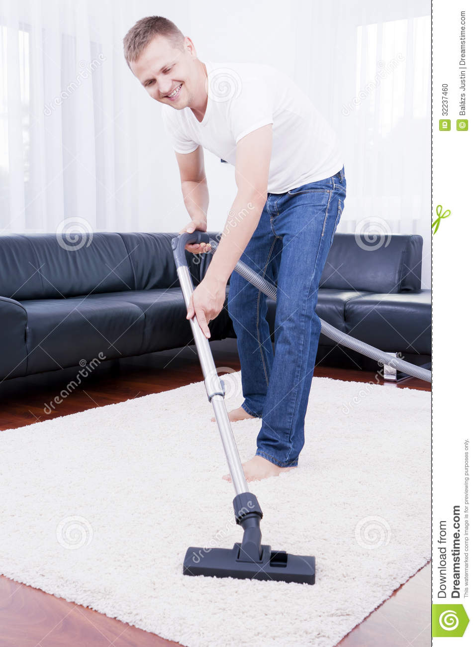 Happy Man Is Cleaning In The Modern Room With Vacuum Stock Photo