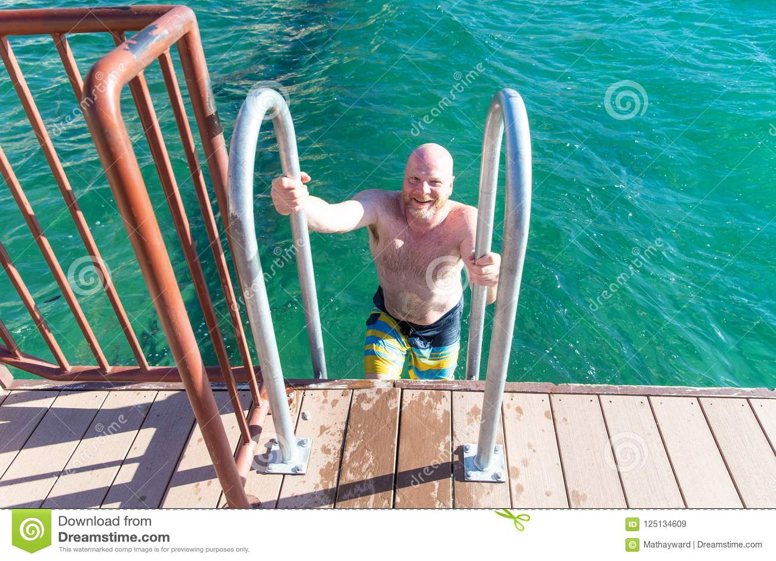 Shirtless, bald man climbing out of lake on a ladder