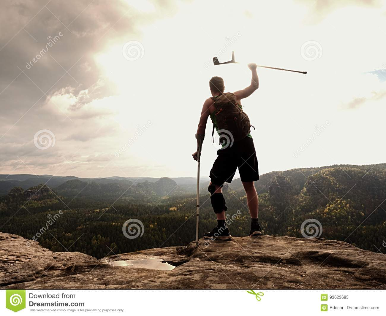 Happy man hiker holding medicine crutch above head, injured knee fixed in knee brace feature.