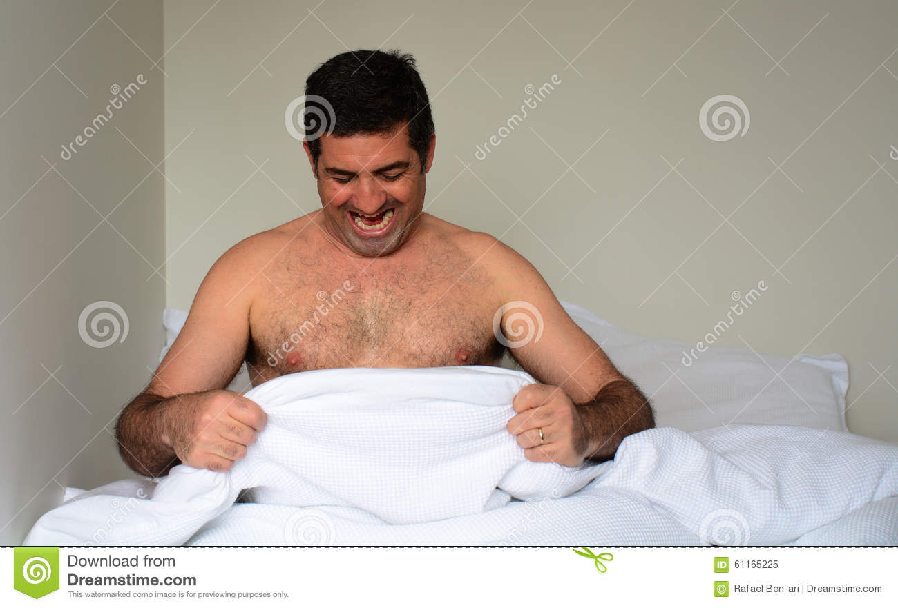 happy man in his forties 40s in bed looking down at his