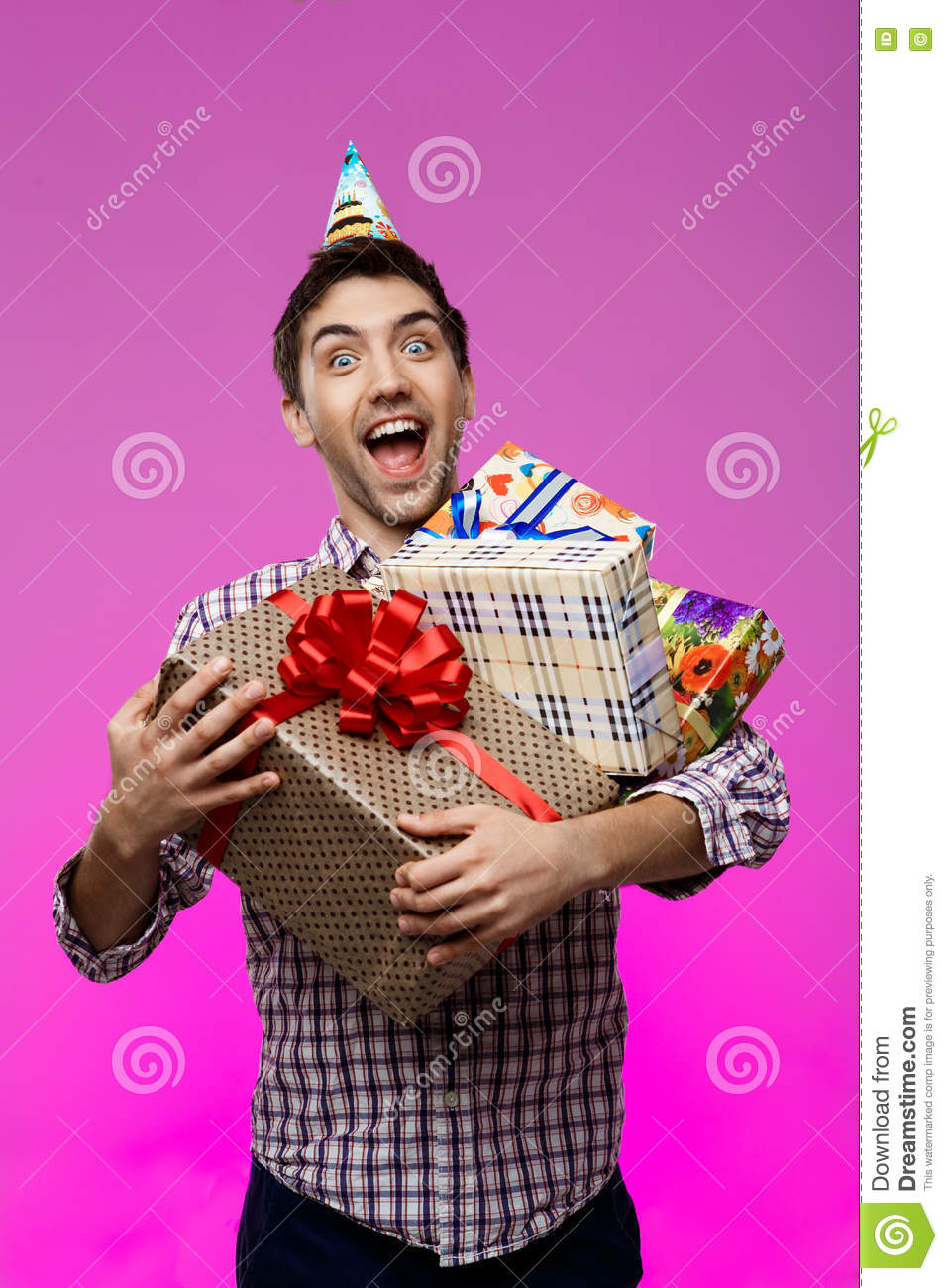 Happy Man Holding Birthday Gifts In Boxes Over Purple Background
