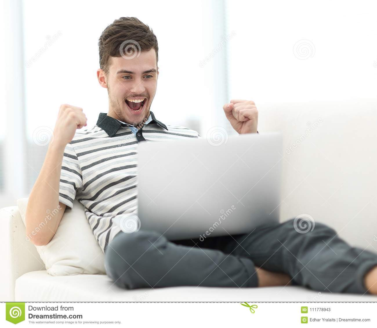Happy man with laptop sitting on the couch
