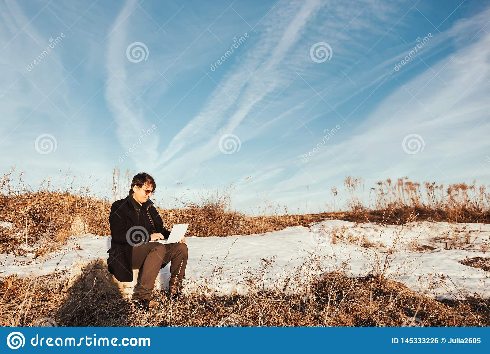 Happy man with laptop in the wheat field.