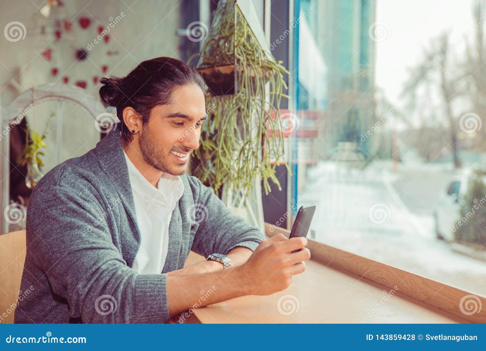 Happy man looking at phone smiling, texting