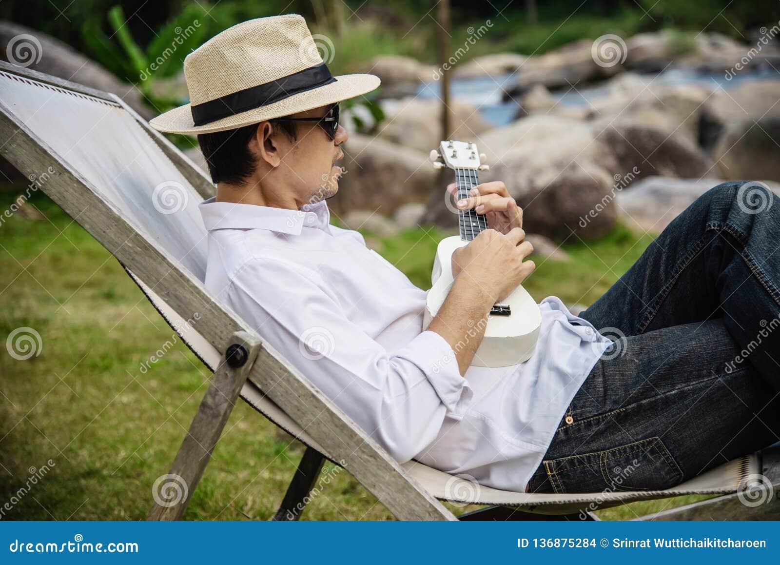 Happy man play guitar in green nature garden