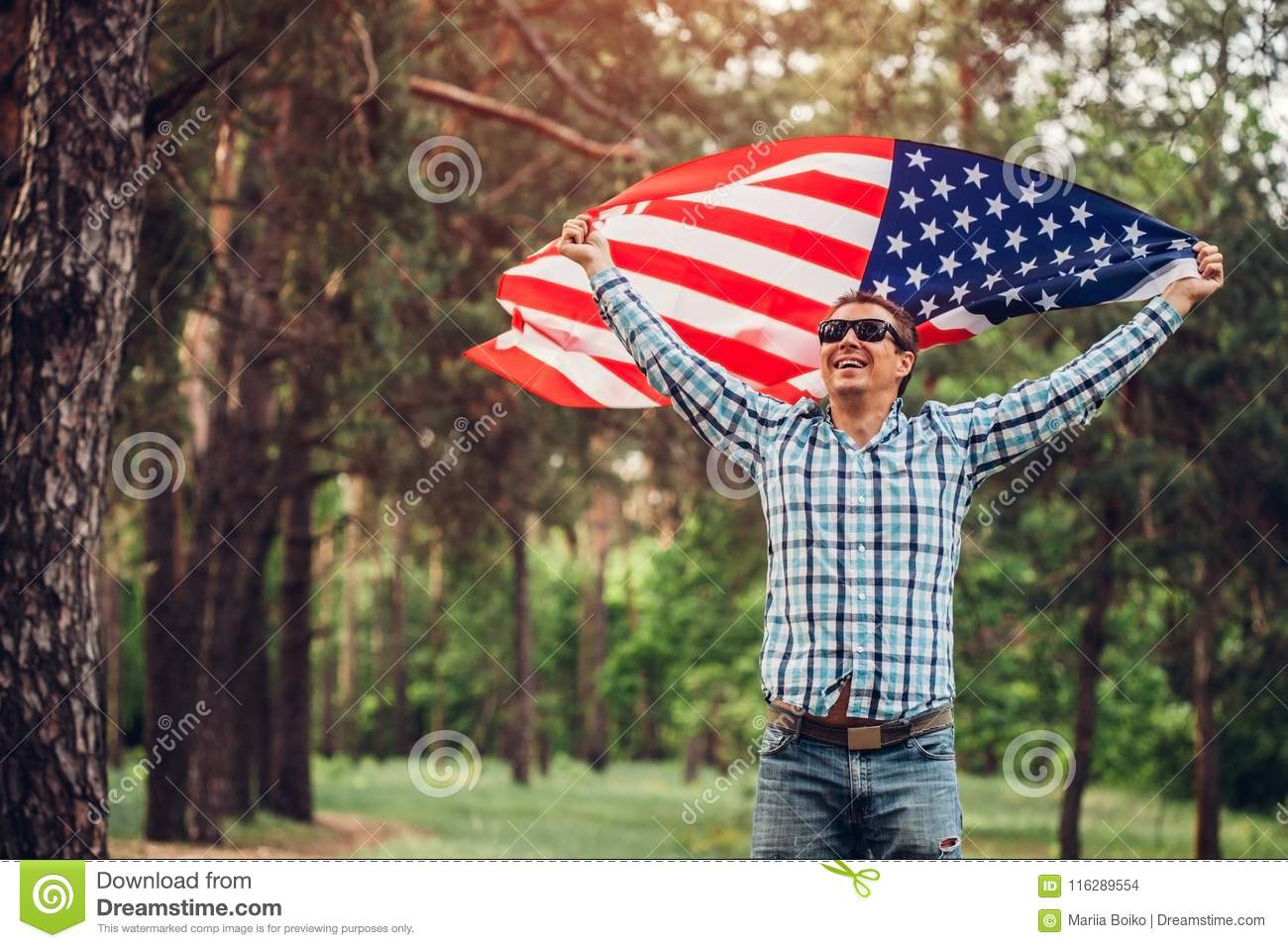 Happy man running with USA flag. Celebrating Independence Day of America. July 4th. Man having fun