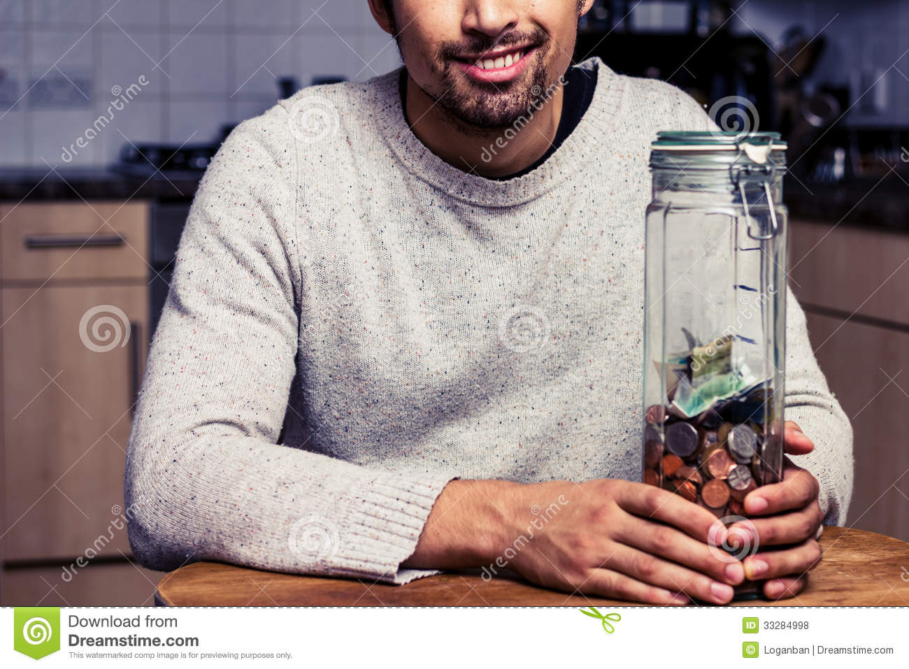 Happy man sitting in kitchen with piggy bank royalty free Large piggy banks for adults