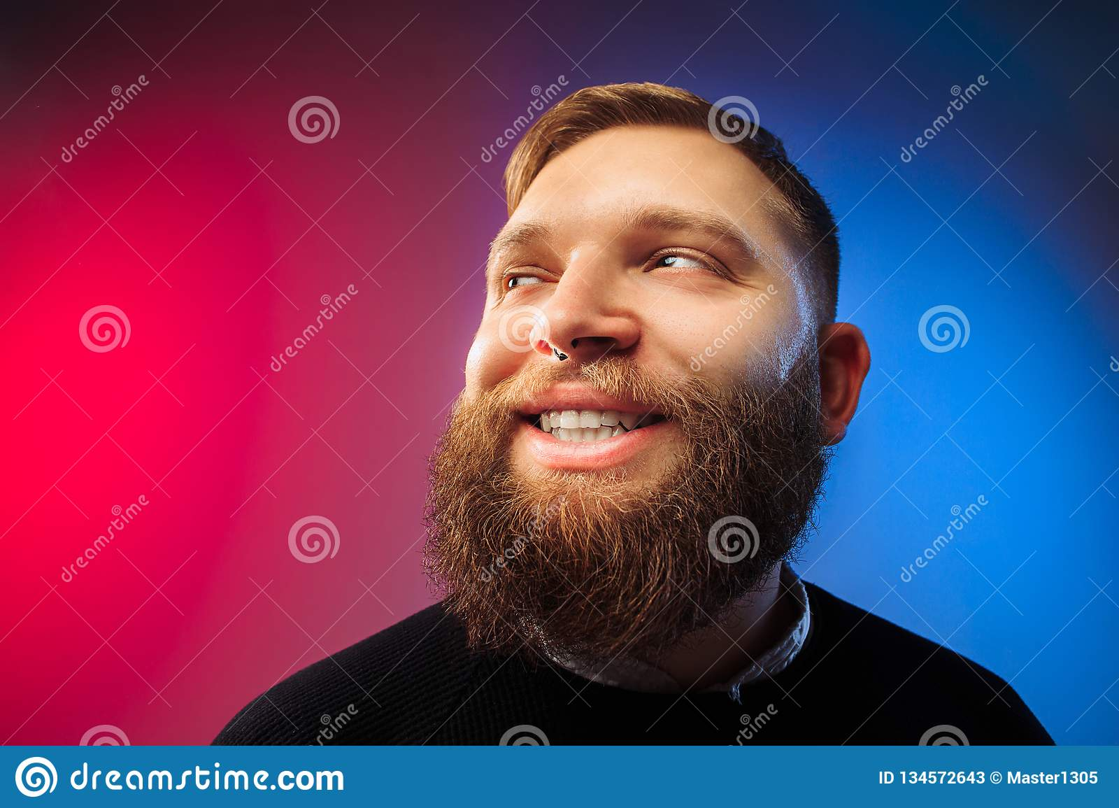 The happy man standing and smiling against pink background.
