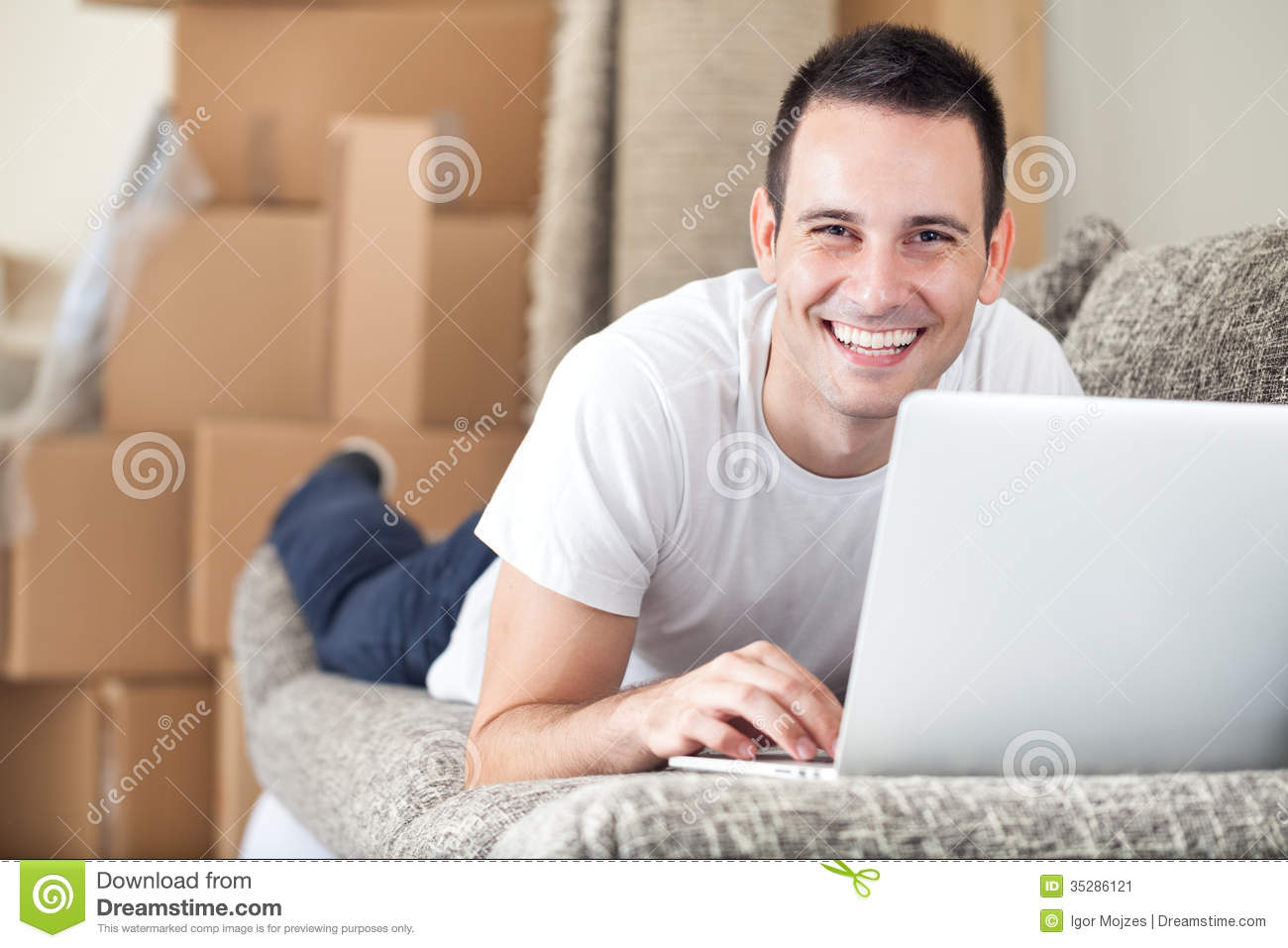 Happy man using laptop in his new home