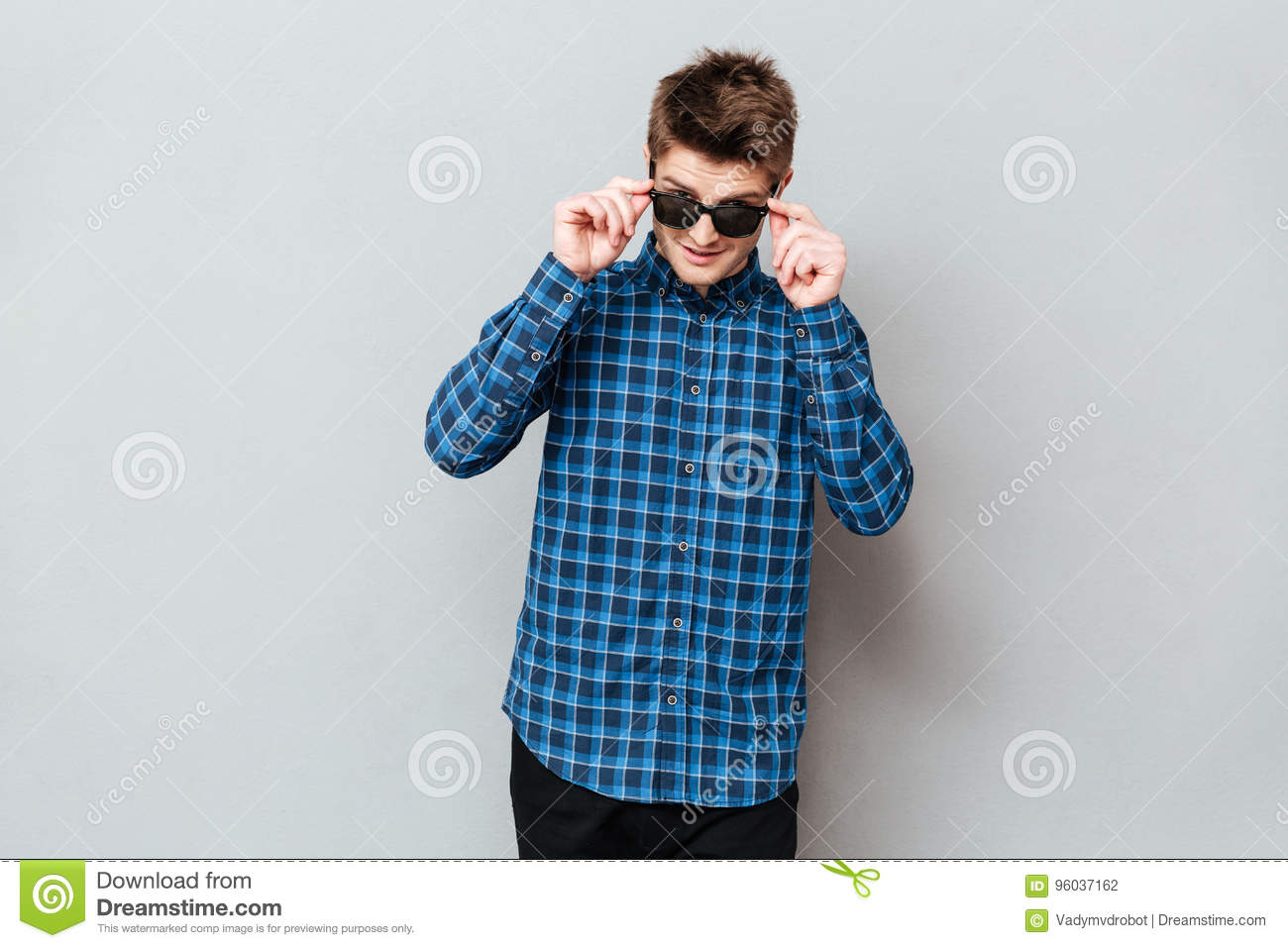 Happy man wearing sunglasses standing over grey wall