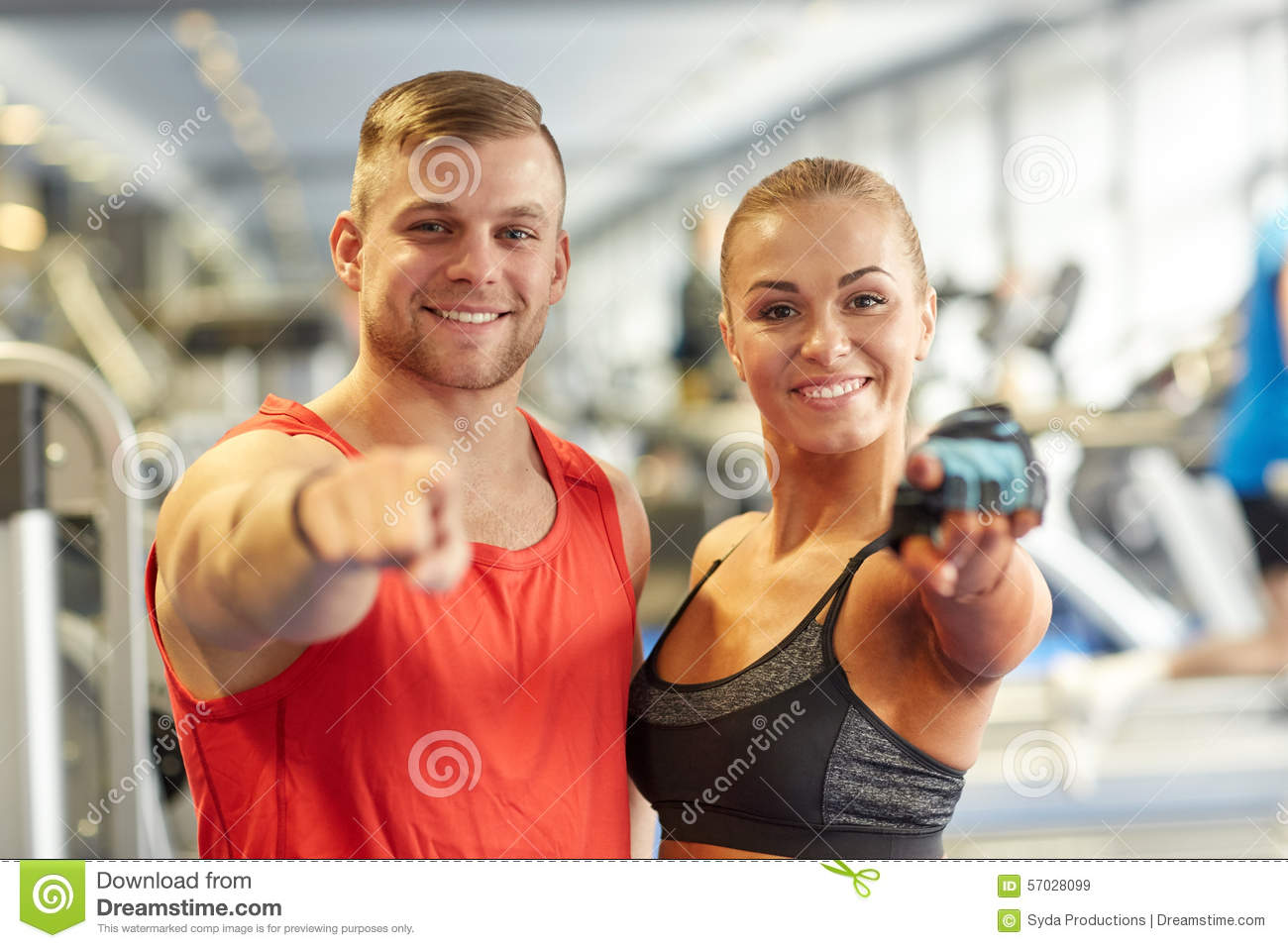 Happy Man And Woman Pointing Finger To You In Gym Stock