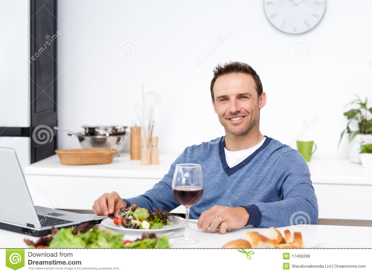 happy man working his laptop having lunch 17469288