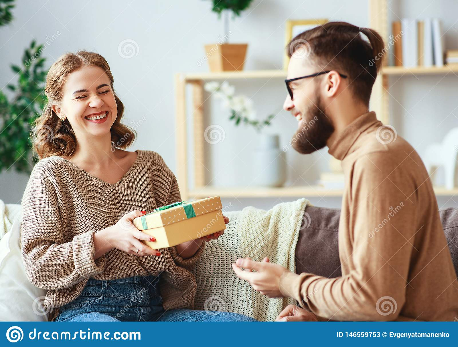 Happy married couple man and woman give a gift for holiday