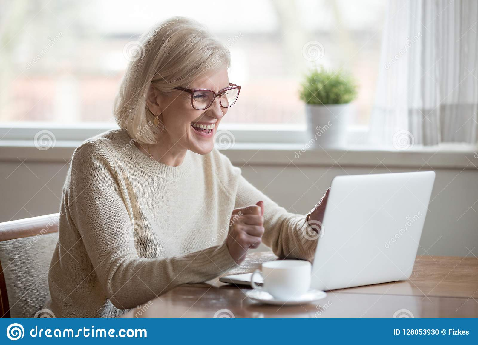 Happy mature businesswoman excited reading good news looking at