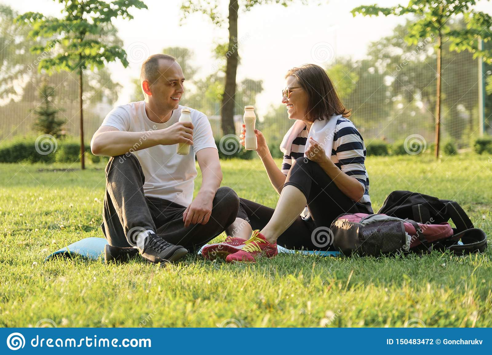 Happy mature couple sitting in the park on fitness mat, resting drinking yogurt after sports exercises