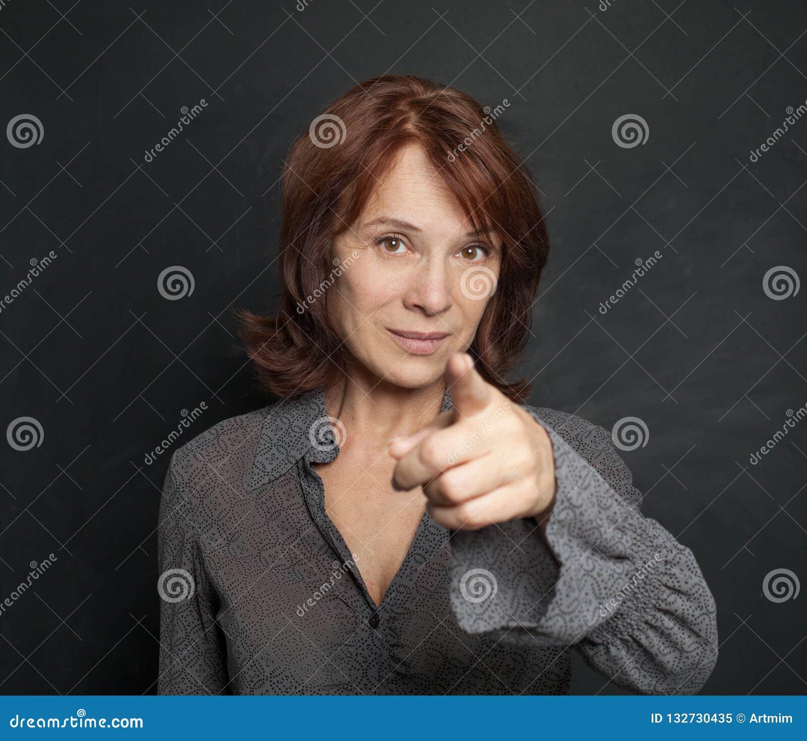 Happy mature woman businesswoman pointing on blackboard