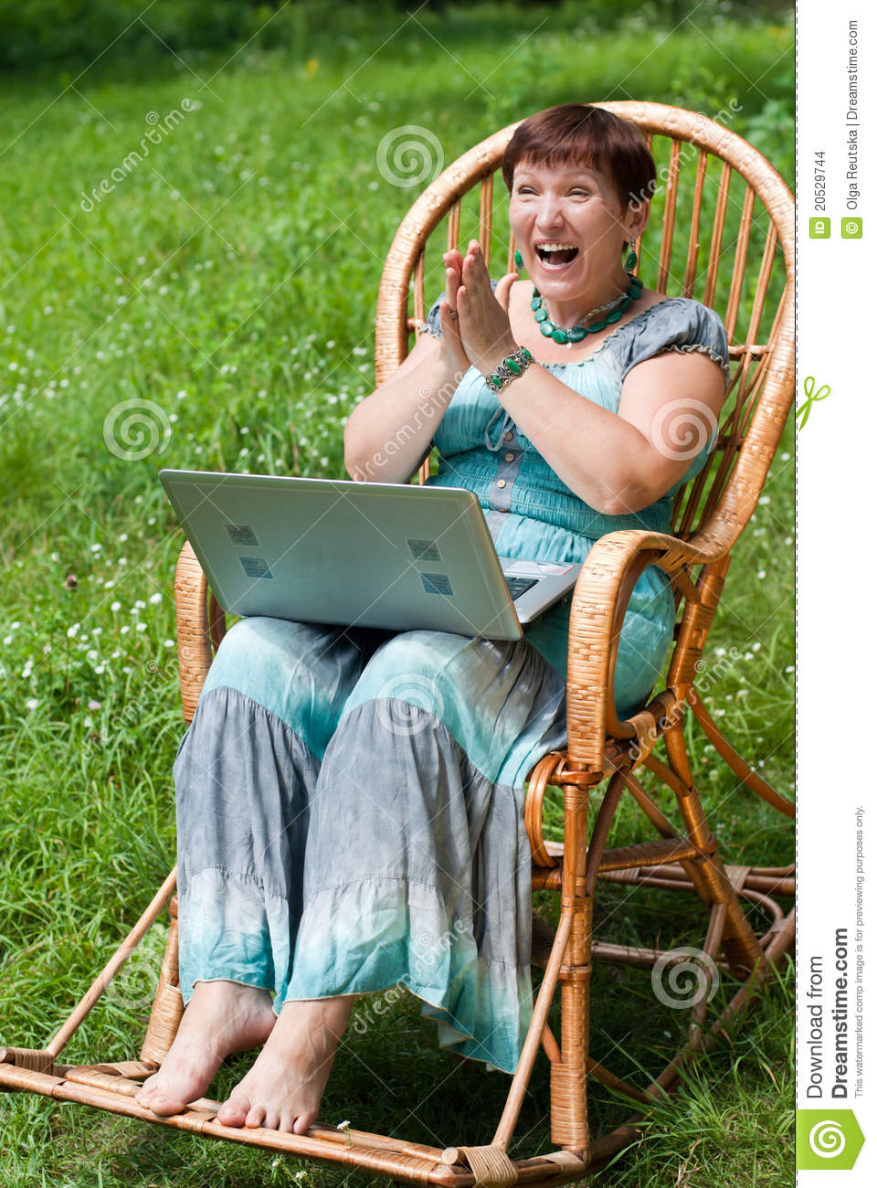 Happy Mature Woman With Laptop In Rocking Chair Stock