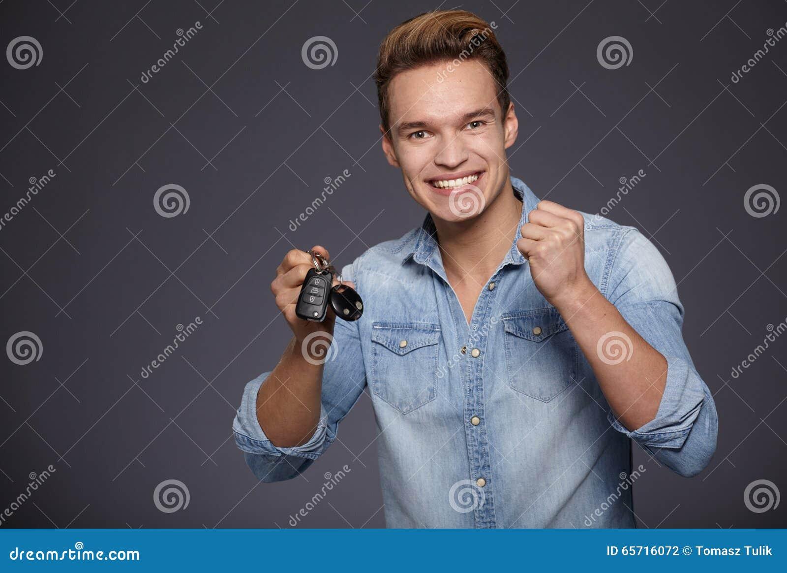 Happy men holding out car keys.