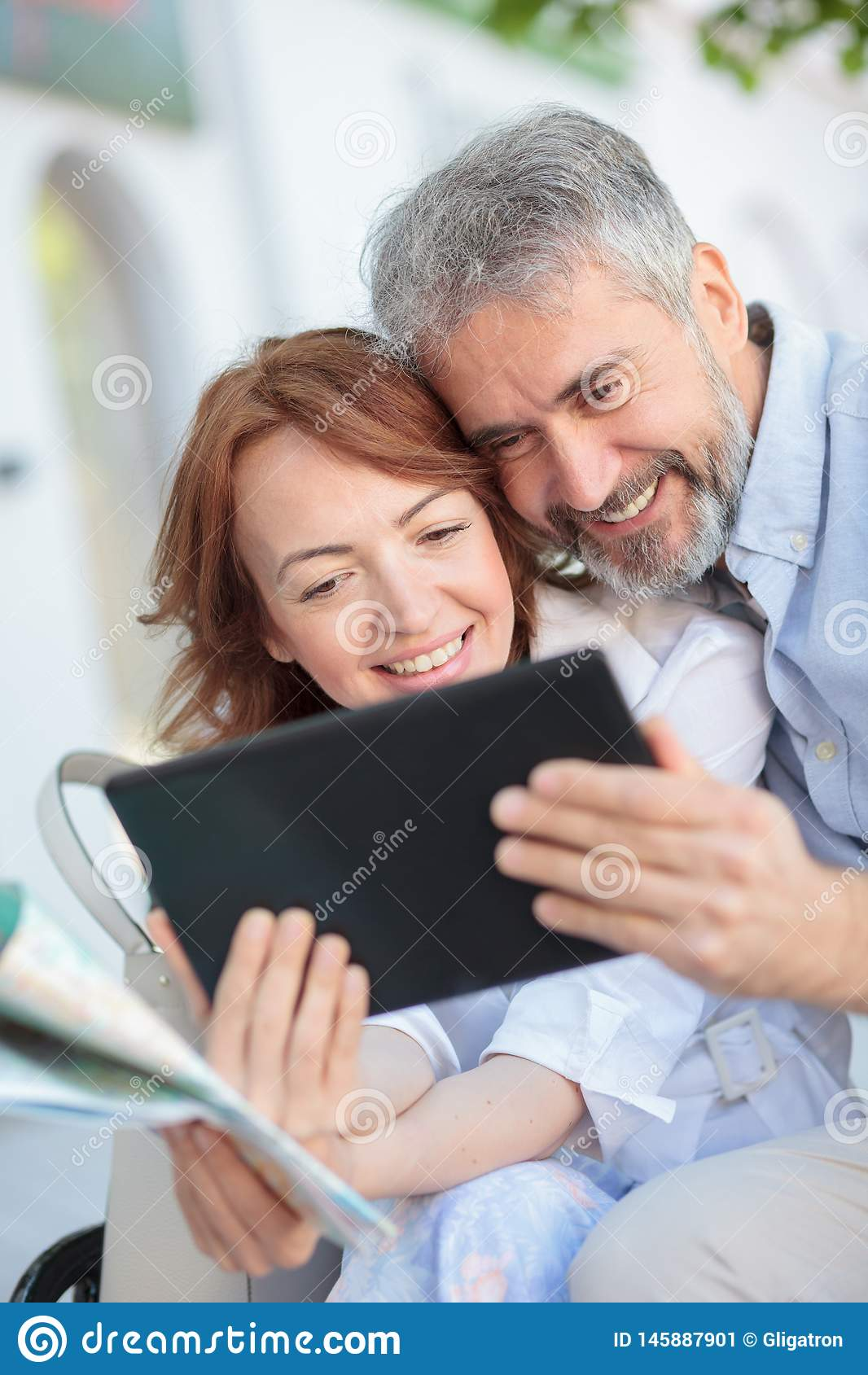 Husband and wife using a tablet while sitting on a bench