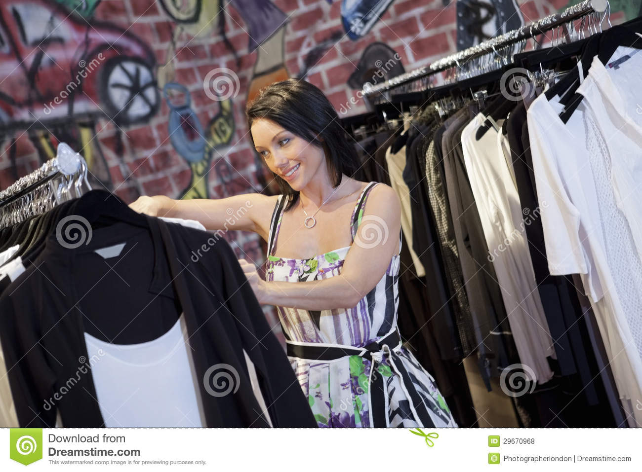 91bf1f0e30888 Happy Mid Adult Woman Browsing Clothes Rack In Fashion Boutique ...