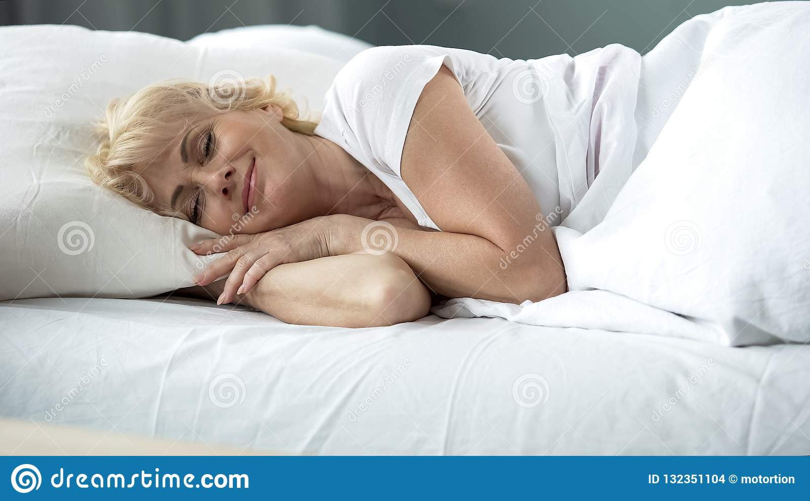 Happy middle-aged female sleeping in bed on orthopedic mattress, healthy rest