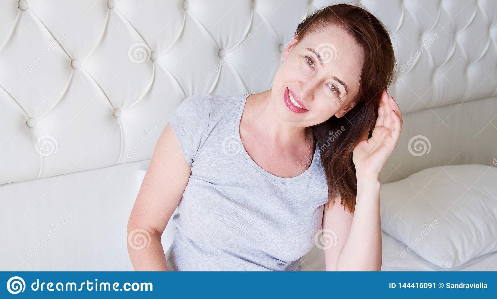 Happy middle aged woman lie in bed. Good morning and sleep concept. Menopause and healthy lifestyle. Selective focus. Banner