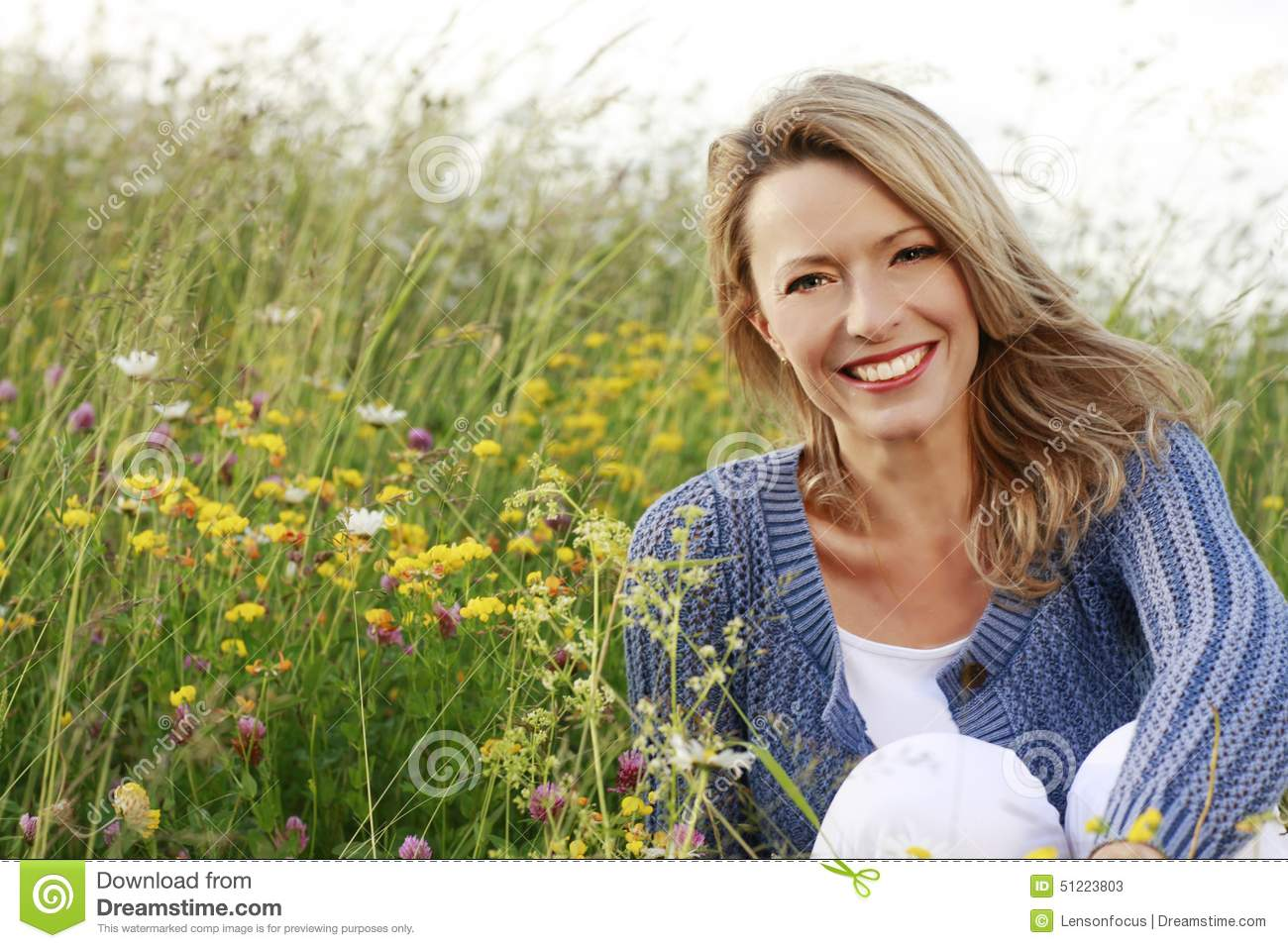 happy-middle-aged-woman-wild-flower-field-smiling-51223803.jpg
