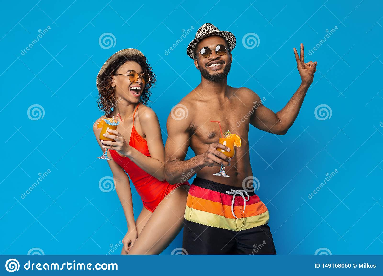 Happy millennial couple in swimwear drinking summer cocktails