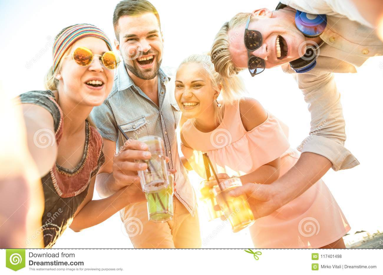 Happy millennial friends group taking selfie at fun beach party
